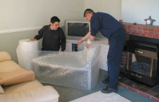 Furniture is wrapped in protective materials.